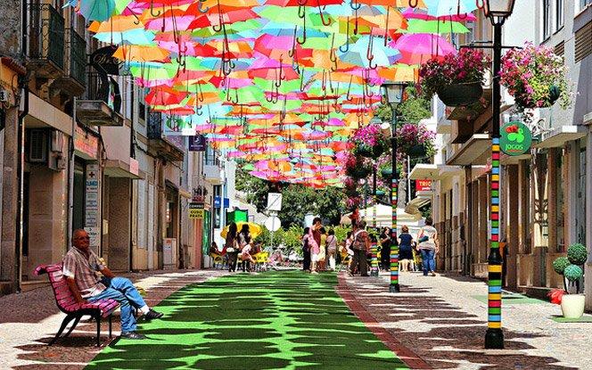 Arte com guarda-chuvas coloridos no meio da rua