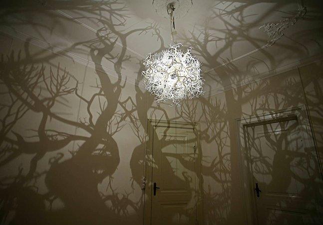 Artistas criam lustre que projeta sombras na parede criando efeito fantástico
