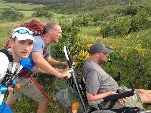 Homem empurra amigo cadeirante pelo Caminho de Santiago
