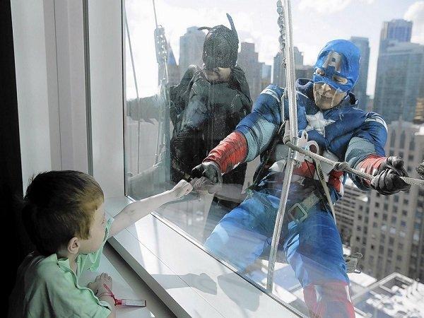 Homens limpam vidros de hospital vestidos de super-heróis para alegrar o dia de crianças internadas