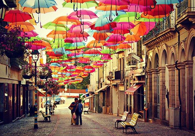 Instalação artística feita com guarda-chuvas enche as ruas de cidade portuguesa durante o verão