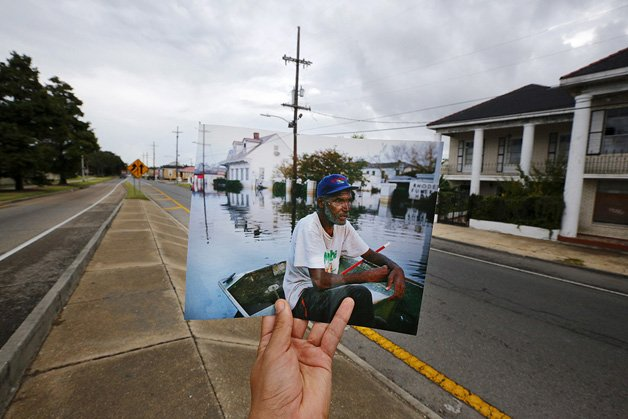 The print shows Errol Morning sitting on his boat on a flooded street September 5, 2005, after Hurricane Katrina struck.