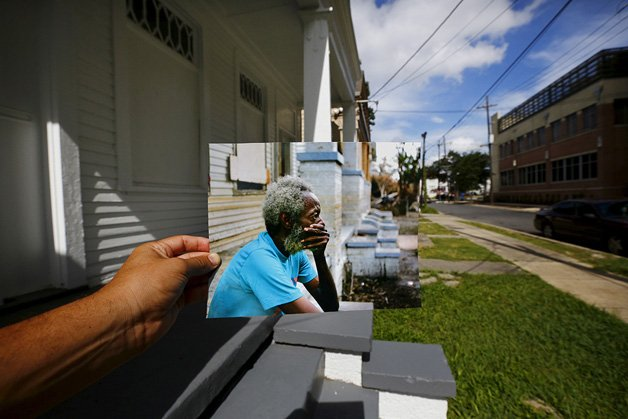The print shows Joshua Creek sitting on the porch of his house, September 13, 2005, after Hurricane Katrina struck.