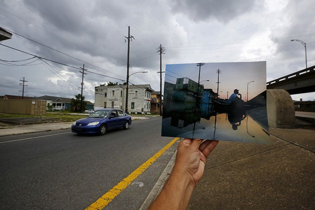 The print shows Errol Morning sitting on his boat on a flooded street, September 5, 2005, after Hurricane Katrina struck.