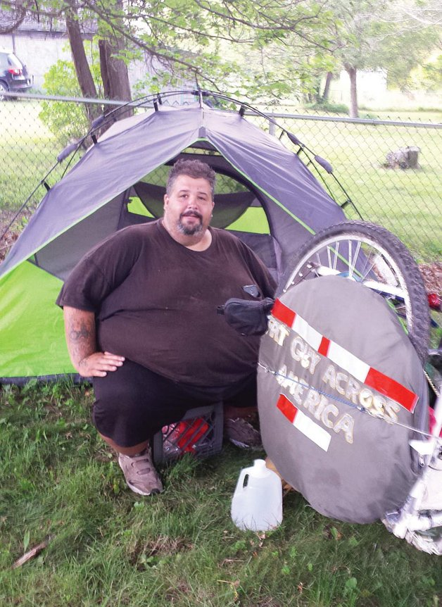 In this July 21, 2015 photo, Eric Hites, rests at the Bliss Congregational Church in Tiverton, R.I., while he waits for a new bicycle so he can continue his cross-country ride. The about 560-pound man is biking across the United States to lose weight. (Marcia Pobzeznik/The Daily News via AP)