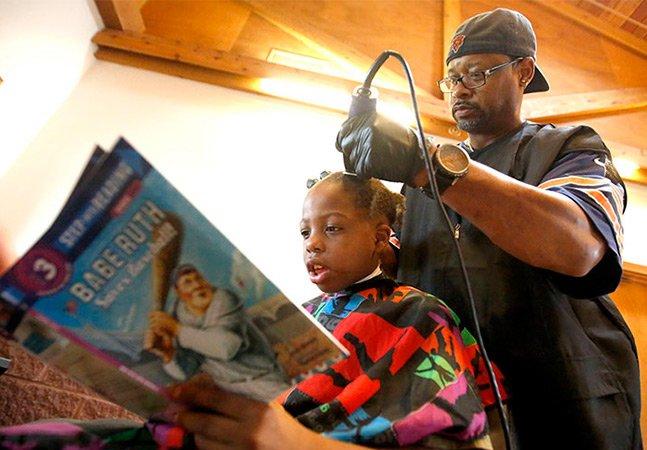 Barbeiro corta cabelo gratuitamente para crianças que lêem para ele