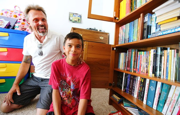 Mail Carrier Ron Lynch, sits with Mathew Flores Sunday, July 26, 2015, in Sandy, near a book shelf now full of books that have been given to Mathew. Mathew approached Ron while he was delivering mail and asked if he had anything he could read.