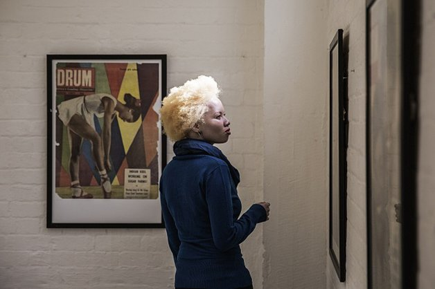 TO GO WITH AFP STORY BY CLAUDINE RENAUD  South African lawyer and part-time fashion model Thando Hopa, an albino, visits an exhibition of Black culture Drum magazine front pages at Arts on Main on June 13, 2015 in Johannesburg. Thando Hopa grew up in the shade, her porcelain skin hidden under long sleeves and sunscreen until the day this South African said goodbye to her complexes and decided to fight prejudice against albinos by becoming a model. Petite and born with a genetic anomaly that left her skin de-pigmented from head to toe, Hopa entered the fashion world without the usual vital statistics required of a catwalk model. But ghostly, no make-up barring a vivid fuchsia on her lips, her hair sculpted to a magnificent bleached height, she exploded onto the cover of the first Forbes Life Africa back in 2013. AFP PHOTO / GIANLUIGI GUERCIA        (Photo credit should read GIANLUIGI GUERCIA/AFP/Getty Images)