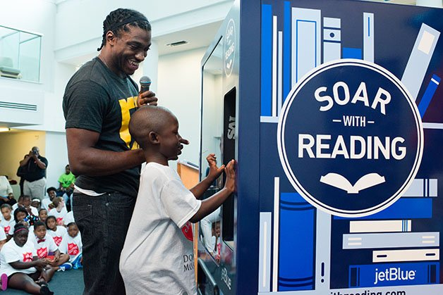 WASHINGTON, DC - JULY 8:  Redskin's Robert Griffin III, left, and Jacob Adams, 5, of DC, use the vending machine at The Salvation Army in Anacostia. On Wednesday, July 8, 2015, JetBlue's Soar with Reading program unveiled its first-of-its-kind book vending machines throughout SE in DC. These vending machines allow kids in the community to receive free books. This initiative is a in response to a study that found Anacostia to be a book desert.  (Photo by Sarah L. Voisin/The Washington Post)