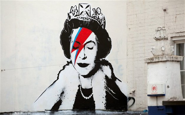 Street artist Banksy is believed to have made his own tribute to the Queen's Diamond Jubilee celebrations - by stenciling this picture of Her Majesty as ZIGGY STARDUST. See SWNS story SWBANKSY; The graffiti expert is reportedly behind the painting, which shows the crown-wearing monarch sporting a jagged red stripe, just like the 1970s David Bowie creation. Her Majesty's startling image - which sprang up as the country celebrated her 60 years on the throne - appeared on a wall previously used by Banksy. Spectators stopped to stare at the stencil, on Upper Maudlin Street, near the Bristol Children's Hospital in the artist's home city.