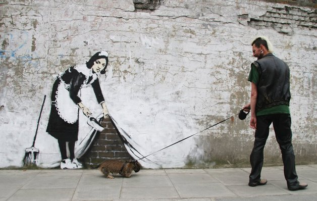 LONDON - MAY 16: Graffitti art by the 'guerilla' artist Banksy is seen on May 16, 2006 in Chalk Farm, London. The striking large scale spray-painted image entitled 'Sweeping It Under The Carpet' depicts a maid who cleaned the artist's room in a motel in Los Angeles. The piece commissioned by 'The Independent' newspaper edited on Tuesday by U2's frontman Bono, is intended to represent a metaphor for the west's reluctance to tackle issues such as Aids in Africa. (Photo by Dave Etheridge-Barnes/Getty Images)