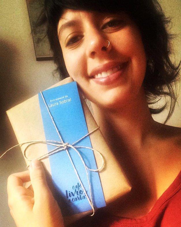 A leitora Laura Sobral com uma de suas encomendas