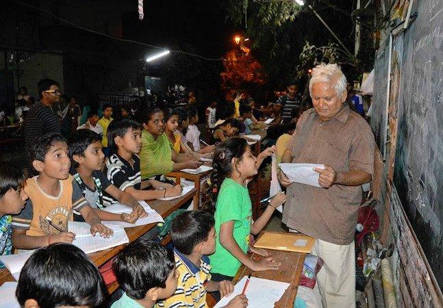 Homem cria escola na rua para ensinar crianças de comunidade na Índia a ler e escrever