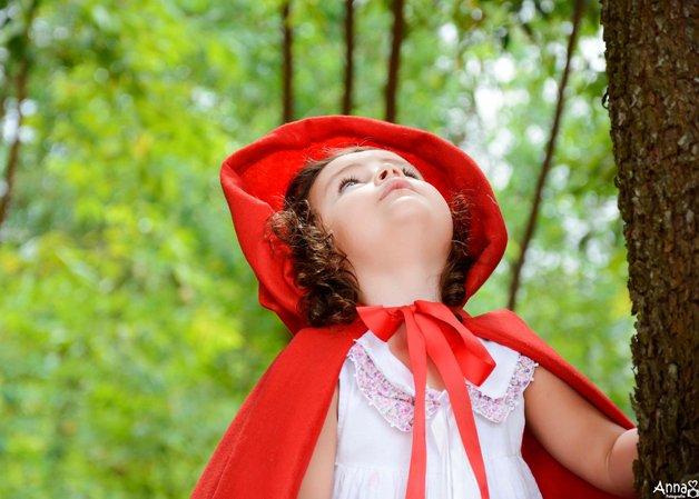 """Um dia, com um retalho de tecido vermelho, sua mãe costurou para ela uma longa capa com capuz; Daquele dia em diante, a menina não quis mais saber de vestir outra roupa, senão aquela e, com o tempo, os moradores da vila passaram a chamá-la de """"Chapeuzinho Vermelho""""."""