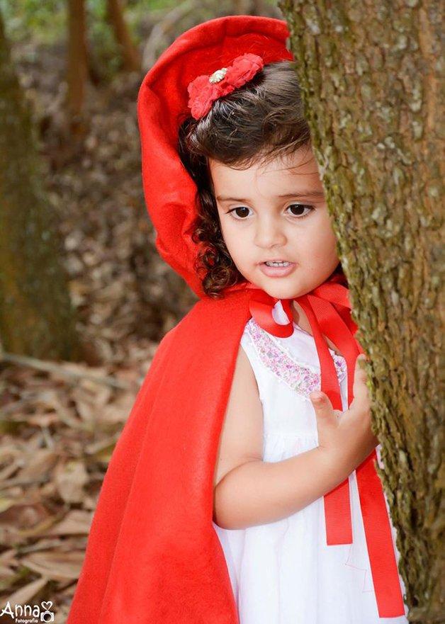 A menina ia por uma trilha quando, de repente, apareceu-lhe na frente um lobo enorme, de olhos brilhantes.