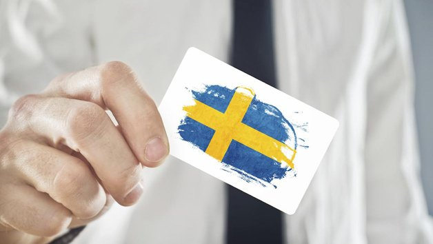 Swedish Businessman holding business card with Sweden Flag