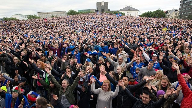 Icelandic soccer fans celebrate as they watch the Euro 2016 round of 16 match between Iceland and England shown on a screen in Reykjavik, Iceland, Monday June 27, 2016. Iceland pulled off the shock of the European Championship by beating England 2-1 in the round of 16 on Monday, continuing the improbable run of the smallest nation at the tournament. (AP Photo/Brynjar Gunnarsson)