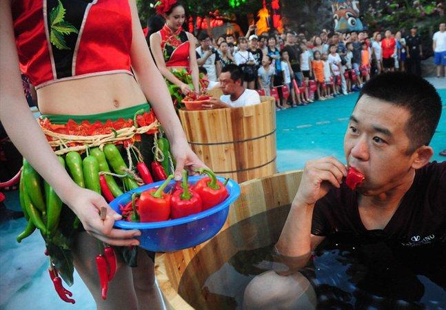 A bizarra competição de quem  come mais pimenta em que os  participantes ficam dentro de tinas de gelo