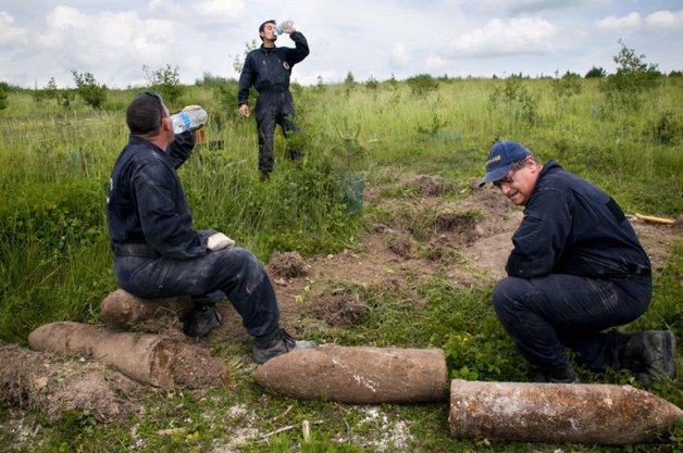 Des démineurs se rafraichissent pendant une courte pause. Lors d'une plantation de jeunes sapins, des sylviculteurs ont décélé la présence possible de munitions. Après un rapide sondage du terrain fait par les démineurs du centre de Châlons-en-Champagne, ceux-ci découvrent à quelques centimètres sous terre, plusieurs obus allemands de 210 mm. Ceux-ci n'ont jamais été tiré et sont probablement les vestiges d'un dépôt de munitions sur le front de 1915. Ces obus pèsent environ 120 kilos chacun.