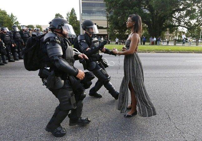 Fotografia de mulher negra parada  diante da polícia americana vira símbolo da tensão racial no país
