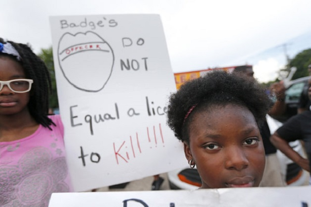 Ja'Sha Triplett, right, and Kemijah Bowie, left, hold signs as people gather outside the Triple S convenience store in Baton Rouge, La., Wednesday, July 6, 2016. Alton Sterling, 37, was shot and killed outside the store by Baton Rouge police, where he was selling CDs. (AP Photo/Gerald Herbert)
