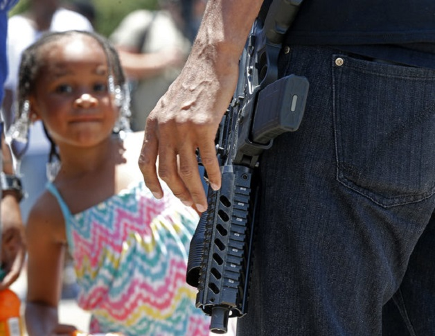 A child stands nearby as Jasiri Basel, an open carry advocate with the group ourbr.org, talks to reporters in front of the Triple S Food Mart in Baton Rouge, La., Thursday, July 7, 2016. Alton Sterling, 37, was shot and killed outside the convenience store by Baton Rouge police, where he was selling CDs. (AP Photo/Gerald Herbert)
