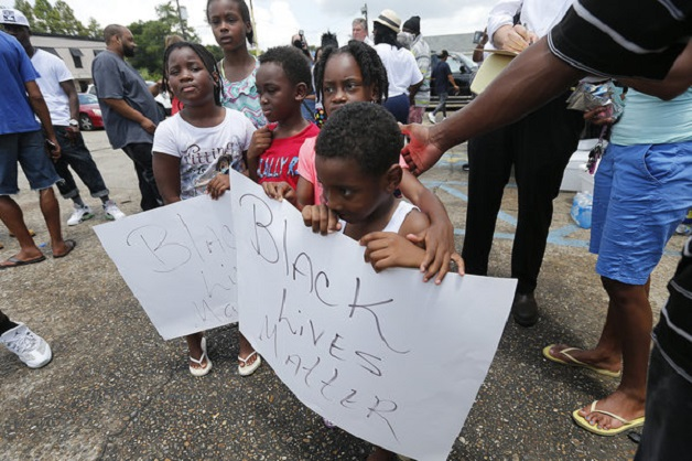 """Children hold signs reading """"Black Lives Matter"""" outside the Triple S convenience store in Baton Rouge, La., Wednesday, July 6, 2016. Alton Sterling was shot and killed outside the store Tuesday by Baton Rouge police, where he was selling CDs. The U.S. Justice Department opened a civil rights investigation Wednesday into the videotaped police killing of Sterling. (AP Photo/Gerald Herbert)"""