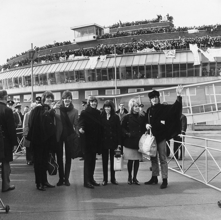 13th March 1965: British pop band The Beatles bidding farewell to their fans at London Airport as they leave to continue production of their film 'Help' in Austria. (Left to right) George Harrison (1943 - 2001), Paul McCartney, Ringo Starr (with Maureen) and John Lennon (1940 - 1980, with Cynthia) (Photo by Dennis Oulds/Central Press/Getty Images)