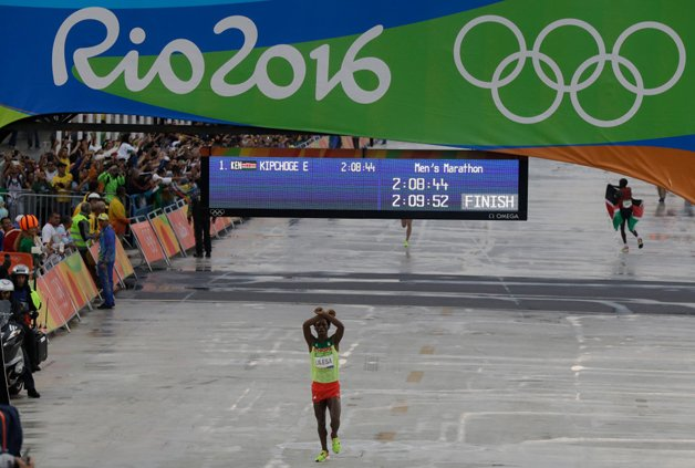 Ethiopia's Feyisa Lilesa crosses his arms as he crosses the finish line to win the silver medal in the men's marathon at the 2016 Summer Olympics in Rio de Janeiro, Brazil, Sunday, Aug. 21, 2016. (AP Photo/Luca Bruno)