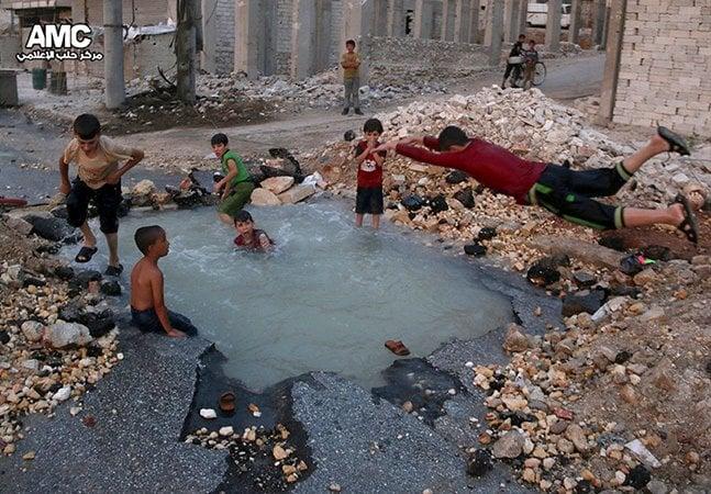 Imagem mostra crianças sírias brincando em piscina formada por buraco de bomba