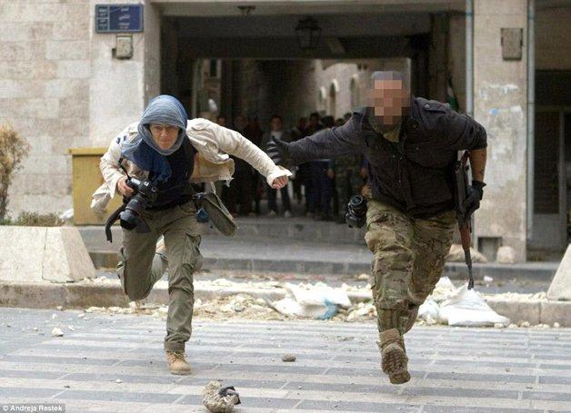 A fotógrafa Andreja Restek, à esquerda, fugindo de tiros em Aleppo, na Síria