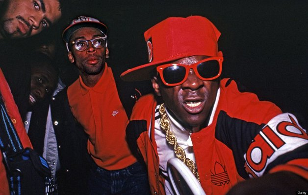 """NEW YORK - SEPTEMBER 15: Flavor Flav (William Jonathan Drayton, Jr.) of Public Enemy (R), Spike Lee (center) and unidentified (L) pose for a photo at a party for the release of Run DMC's album """"Tougher Than Leather"""" on September 15, 1988 at the Palladium night club in New York City, New York. (Photo by Catherine McGann/Getty Images)"""