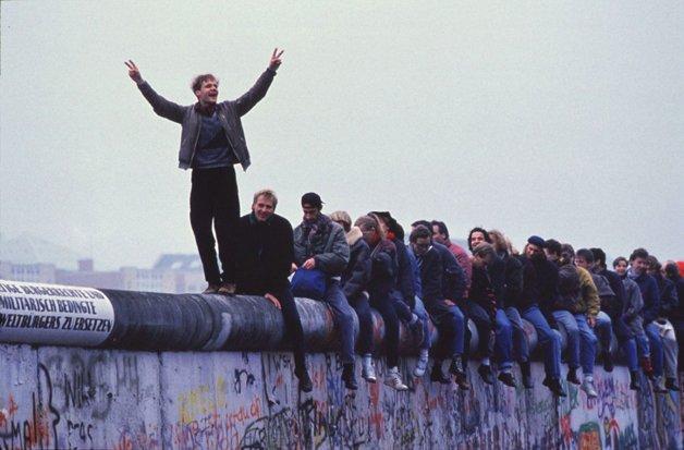 Jovens comemoram a reunificação da Alemanha em cima do Muro