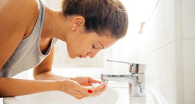 Young cheerful woman having morning hygiene in bathroom