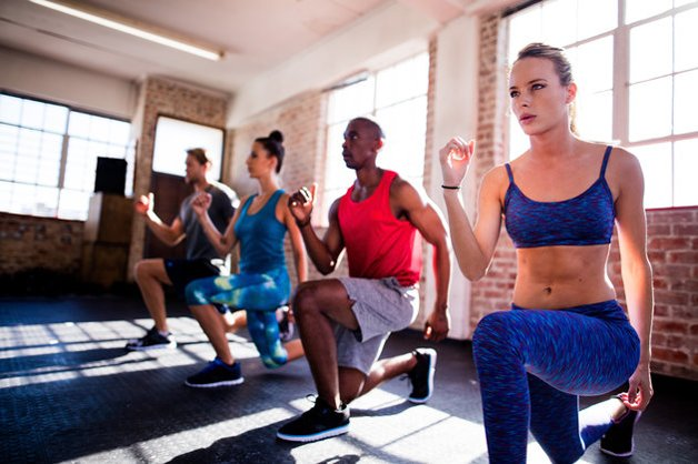Multi-ethnic group of friends doing lunges during a workout in the gym