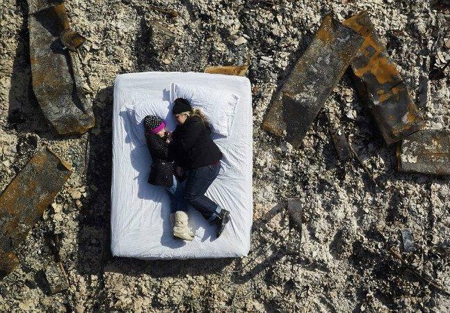 Fotógrafo capta vítimas de incêndio florestal deitadas em colchões brancos no lugar onde ficavam suas casas