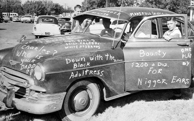 Jovem em um carro coberto por mensagens racistas no Texas em 1956