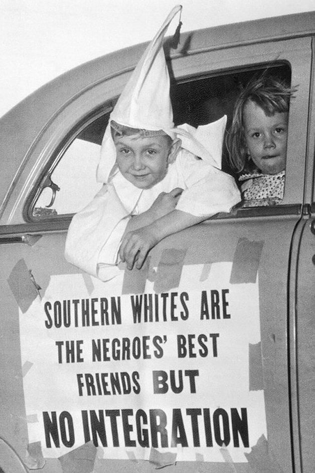 """Criança fantasiada de Ku Klux Klan em uma manifestação racista em 1956. Na porta do carro está escrito """"Brancos do Sul são os melhores amigos dos negros, mas integração não"""""""