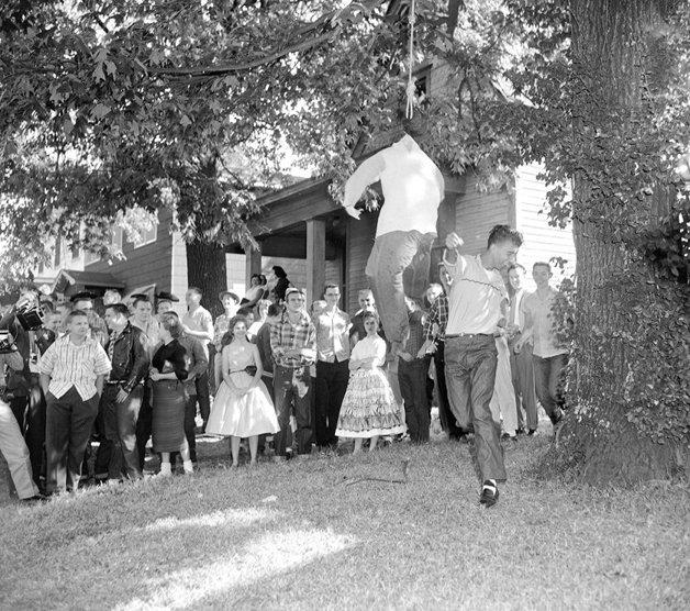 Homem bate em um boneco enforcado em protesto contra a integração racial no Arkansas, em 1957