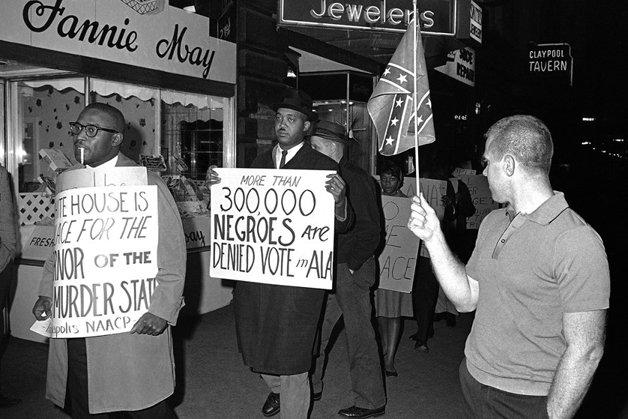 """Homem com bandeira dos Confederados observa manifestantes no Alabama, em 1964. O cartaz diz: """"Mais de 300 mil negros têm seu voto negado em Alabama"""""""