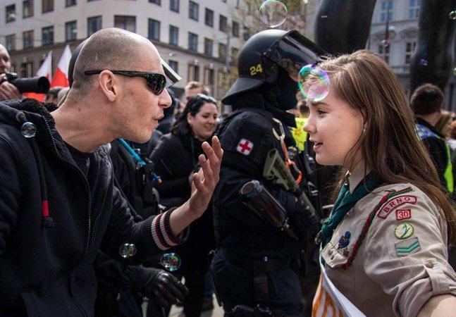 Garota enfrenta ódio neonazista com sorriso e coragem em imagem de luta e amor