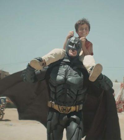 A linda e urgente mensagem por trás do vídeo e das fotos virais de Batman em um campo de refugiados