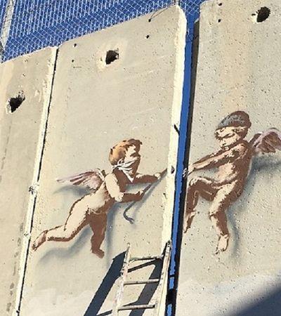 Em nova arte de Banksy, anjinhos abrem fenda em muro que separa Israel de território palestino