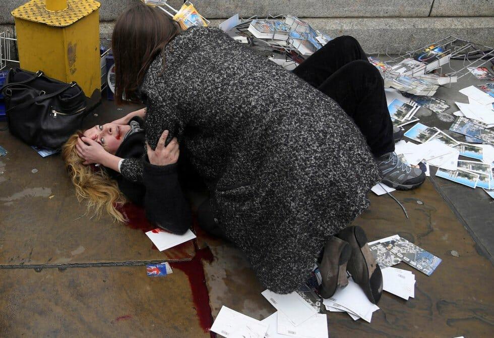 """Mulher ajuda uma das vítimas do atropelamento na ponte de Westminster, em Londres. Foto indicada nas categorias """"Foto do Ano"""" e """"Temas atuais"""", feita pelo fotógrafo Toby Melvill, da agência Reuters."""
