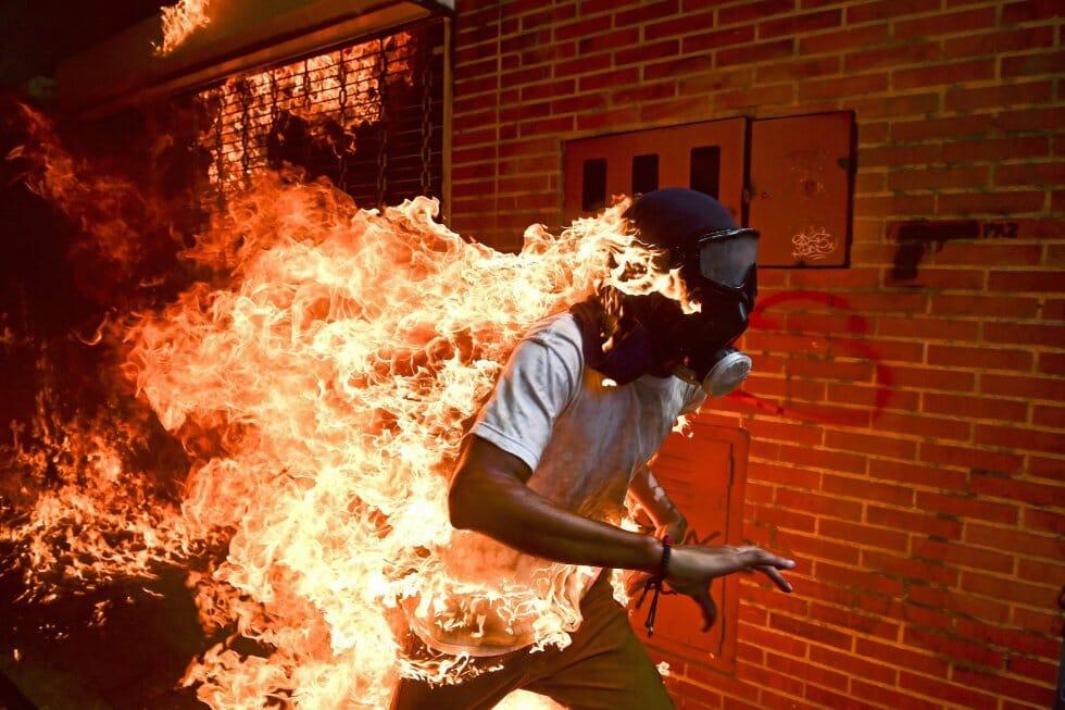 O jovem José Víctor Salazar Balza, 28 anos, corre em chamas durante confrontos violentos com a polícia num protesto contra o presidente Nicolás Maduro em Caracas, Venezuela. Foto indicada nas categorias 'Foto do Ano' e 'Temas da atualidade', feita pelo fotógrafo Romaldo Schemidt, da agência France Presse (AFP).