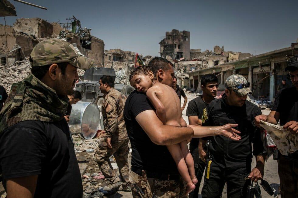 """Criança é levada da última área controlada pelo Estado islâmico na Cidade Velha de Mosul por um homem suspeito de ser militante, atendido por soldados das Forças Especiais do Iraque. Foto indicada na categoria """"Foto do Ano"""", feita pelo fotógrafo Ivor Prickett."""