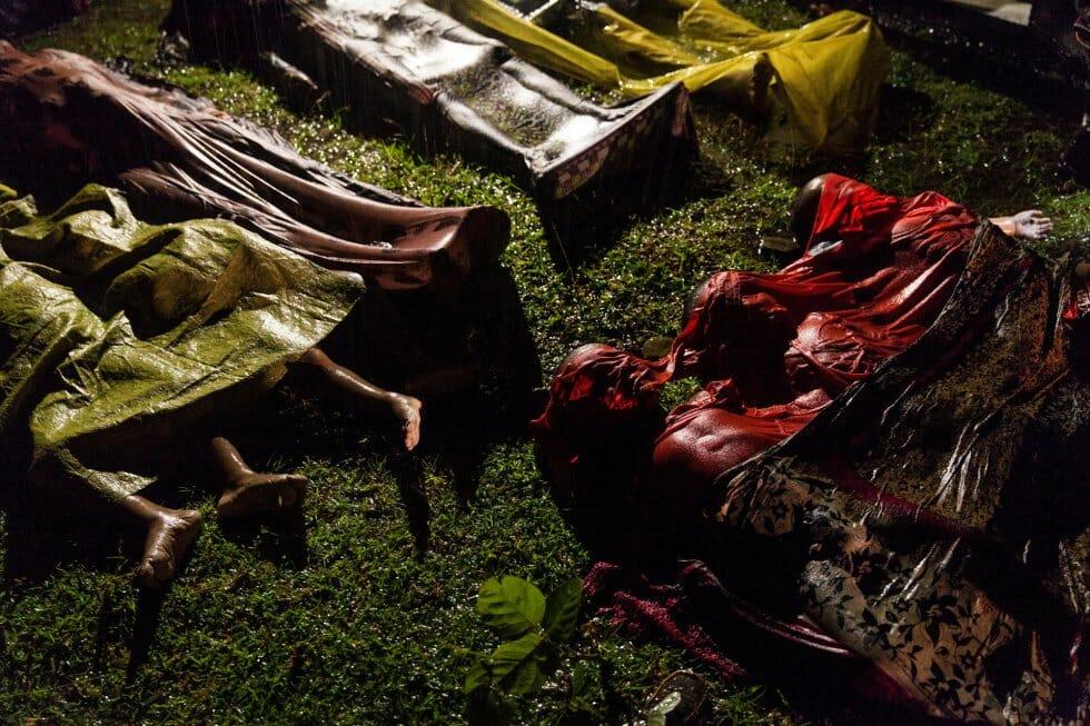"""Corpos de refugiados Rohingya cobertos no chão, mortos após o barco que levava cerca de 100 pessoas de Myanmar para Bangladesh, em 28 de setembro de 2017. Apenas 17 pessoas sobreviveram. Foto feita por feita pelo fotógrafo Patrick Brown, da Panos Pictures para a Unicef, indicada nas categorias """"Foto do Ano"""" e """"Notícias Gerais""""."""