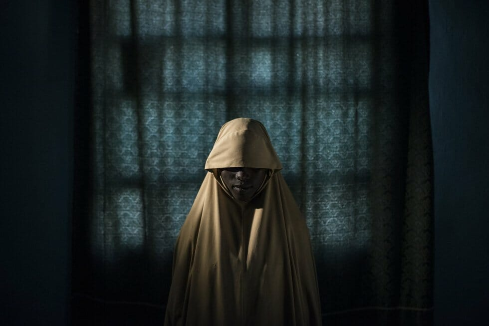 """A jovem Aisha, de 14 anos, foi sequestrada pelo grupo terrorista Boko Haram e forçada a participar de uma missão suicida. Ela conseguiu ajuda e evitou sua morte e a explosão das bombas. Imagem tirada pelo fotógrafo australiano Adam Ferguson para o New York Times, em Maiduguri, na Nigéria, e indicada na categoria """"Foto do Ano""""."""