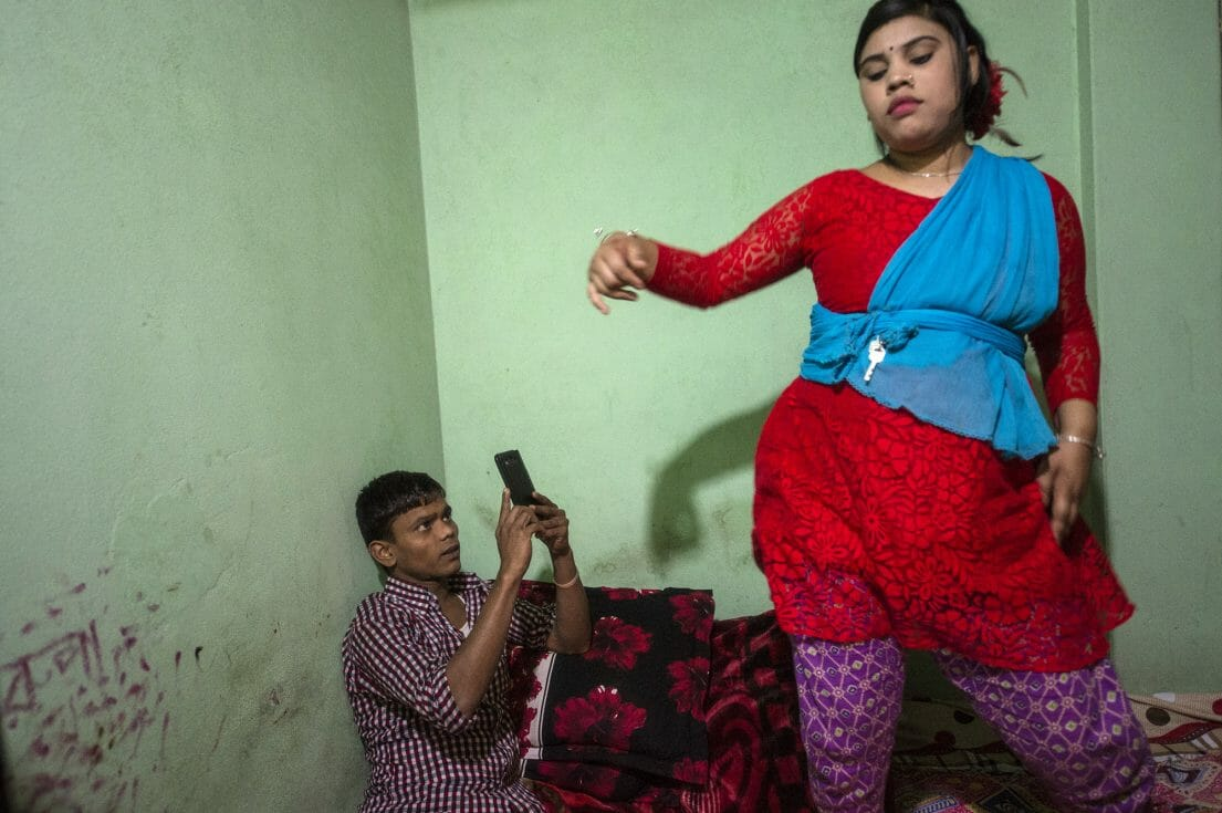 Rupa, 16, is dancing on the bed while a customer is filming her.