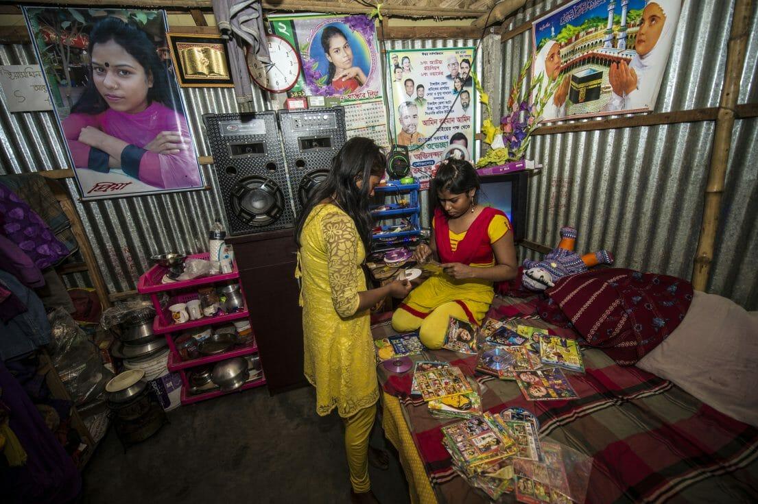 Priya and Kajol are looking for music in Priya's room.